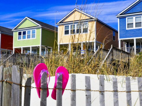 Row of beach rentals on a summer day, pink flip flops on beach fence; Courtesy of StacieStauffSmith Photos/Shutterstock
