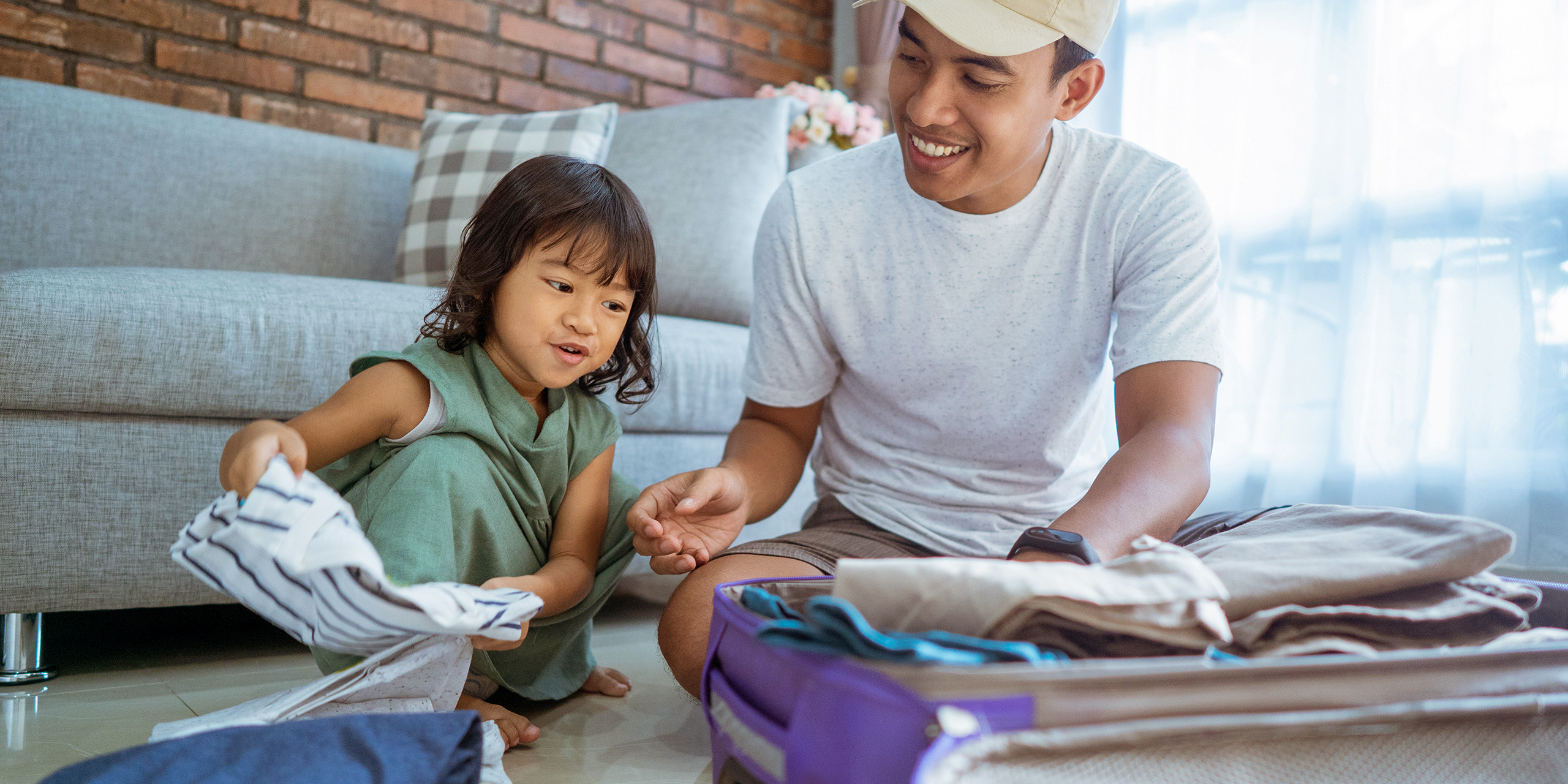 dad and kid happily prepare for holiday. packing up some clothes in suitcase for vacation; Courtesy of Odua Images/Shutterstock