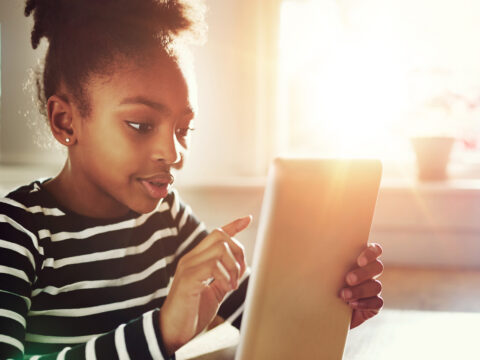 Young African-American Girl Surfing the Internet Using Tablet computer at the Table Inside Home.; Courtesy of Flamingo Images/Shutterstock