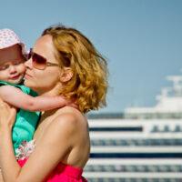 mom holds toddler in front of cruise ship; Courtesy Seleznev Oleg/Shutterstock