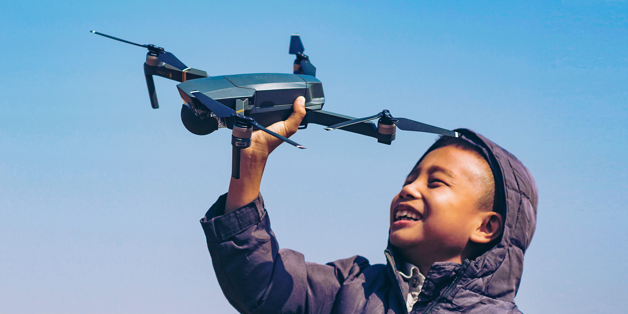boy holding up a drone in field; Courtesy GNT STUDIO/Shutterstock