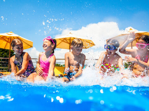 Children play fun with splashes on the side of the pool at the resort; Courtesy of YanLev/Shutterstock