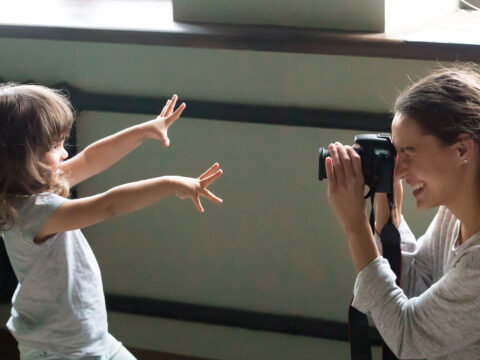 mom taking photo of daughter dslr camera; Courtesy fizkes/Shutterstock