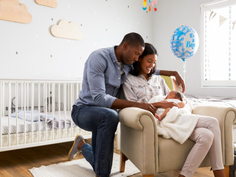 parents holding newborn in baby room; Courtesy Monkey Business Images/Shutterstock