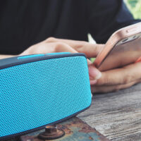 Woman using bluetooth speaker with smart phone; Courtesy successo images/Shutterstock