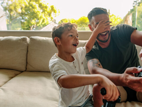 Little boy covering eyes of his father playing video game. Cheerful family of father and son having fun playing video games at home. Courtesy Jacob Lund/Shutterstock
