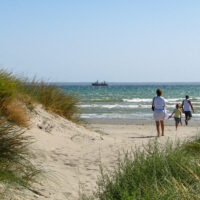 family walking to the beach. sand dunes beach michigan; Courtesy Slniecko/Shutterstock