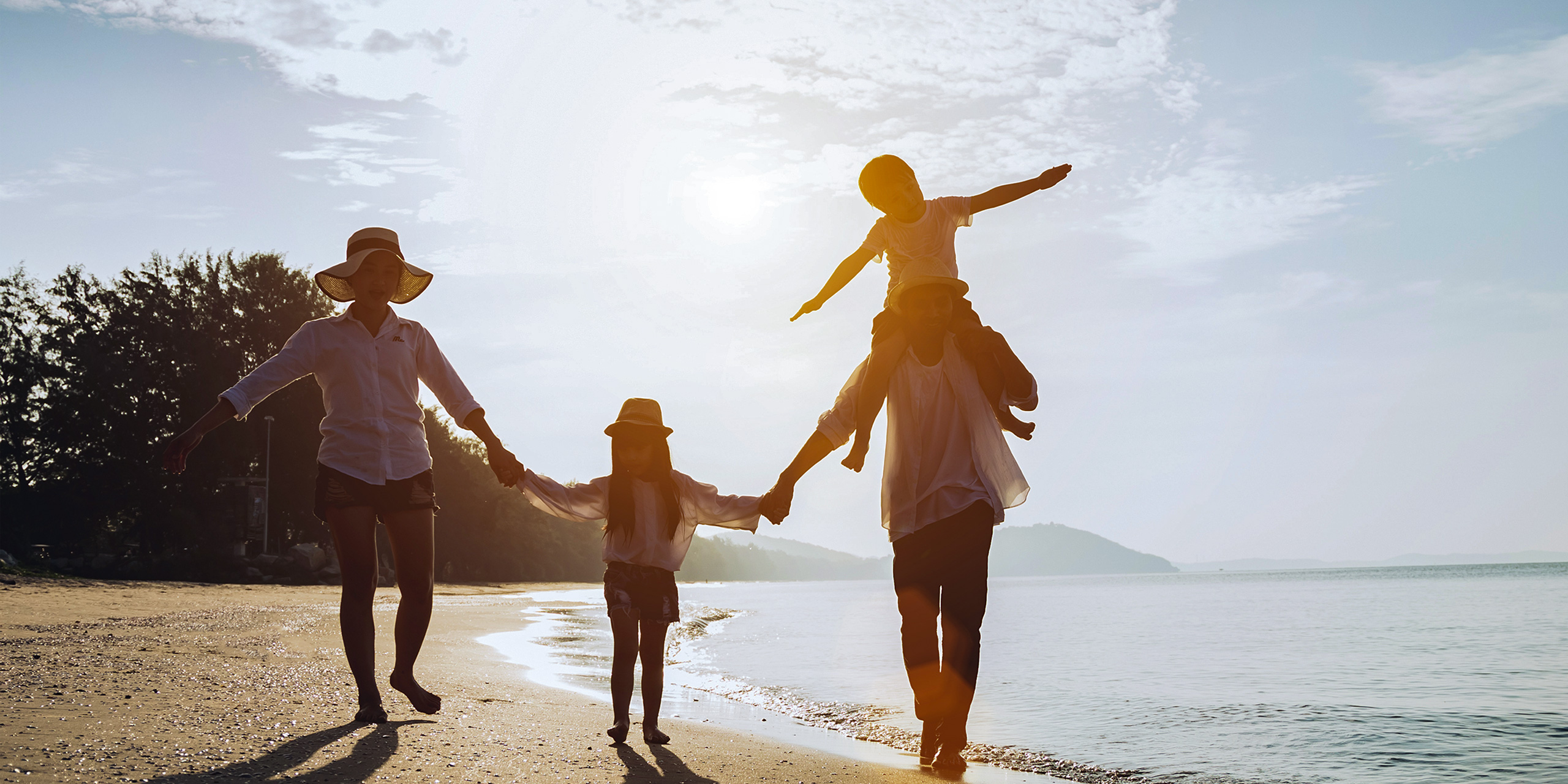 Holiday travel concept, Summer vacations. Happy family are having fun on a tropical beach in sunset. Father and mother and children playing together outdoor on sea.; Courtesy Sumala Chidchoi/Shutterstock