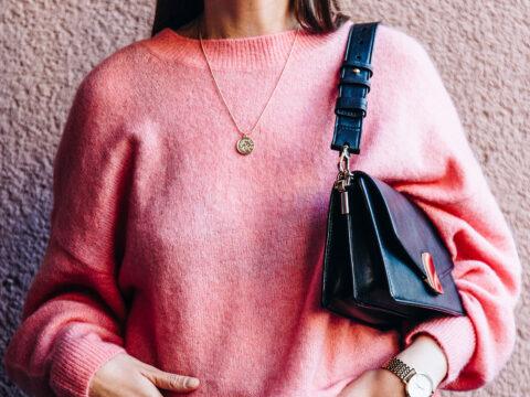 woman wearing pink sweater holding handbag