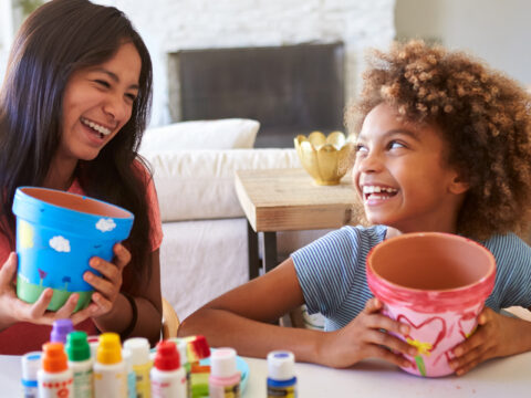 Happy pre-teen girl and her older girlfriend holding plant pots that they've decorated with paints at home, smiling at each other