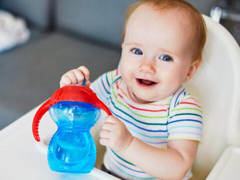 Little baby girl sitting in high chair at home or at restaurant and drinking water from sippy cup; Courtesy Ekaterina Pokrovsky/Shutterstock