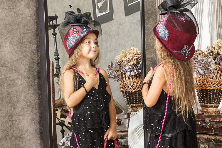 little girl playing dress-up looking in mirror; Courtesy Kuznetsov Alexey/Shutterstock