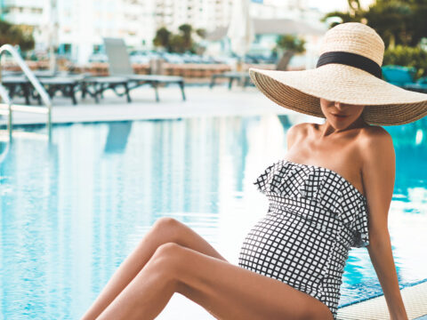 beautiful pregnant woman in straw hat in swimming pool. Beautiful pregnancy. Beauty and health