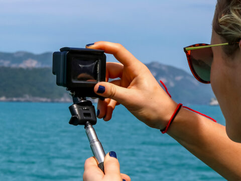 European girl tourists enjoy the GoPro camera and view of the island and the sea on the boat.
