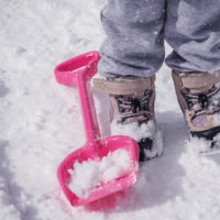 Child wearing snow boots in the snow next to a snow toy shovel