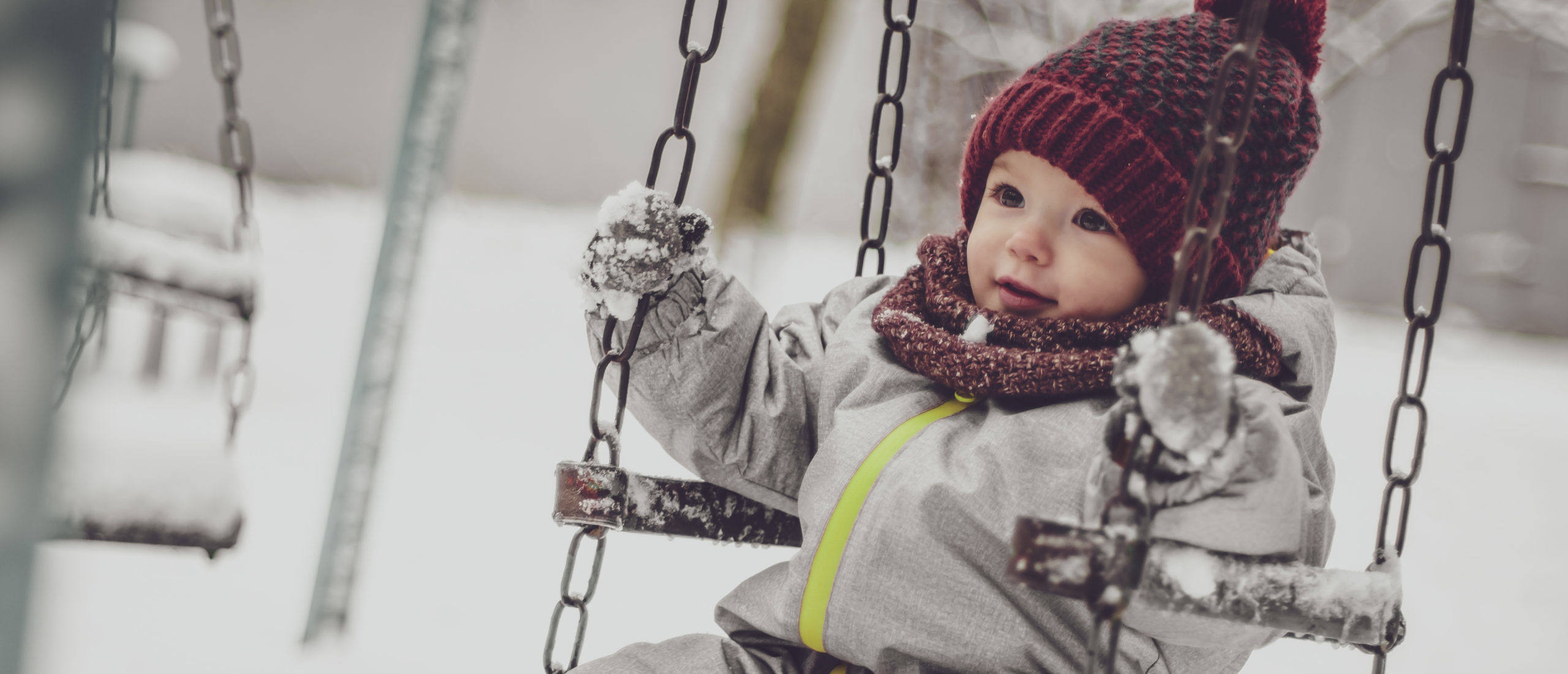 Toddler bundled in snow gear on a swing