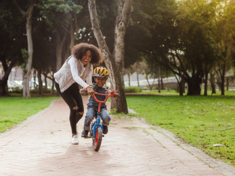 Mom teaching child how to ride a bike