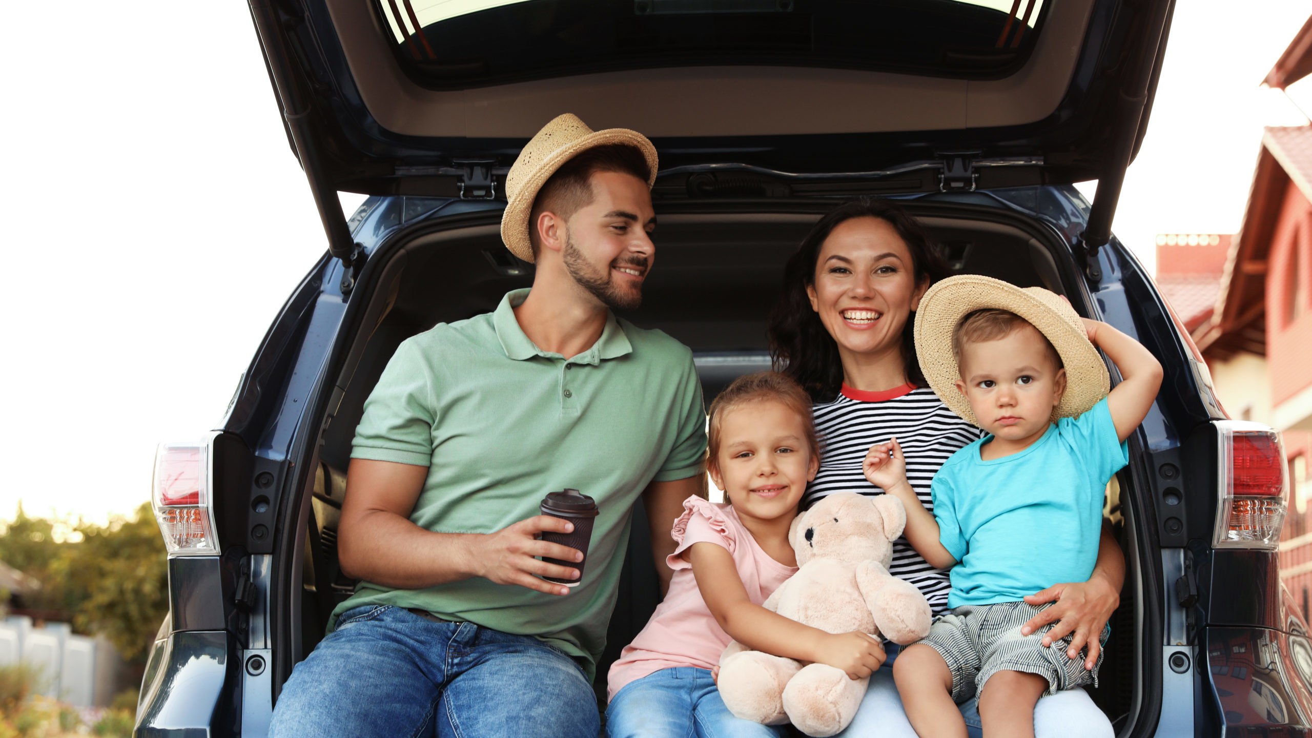 Family of four sitting in the trunk of their car with suitcases nearby