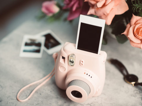 Pink instant camera printing a blank photo on a table with other photos and pink roses