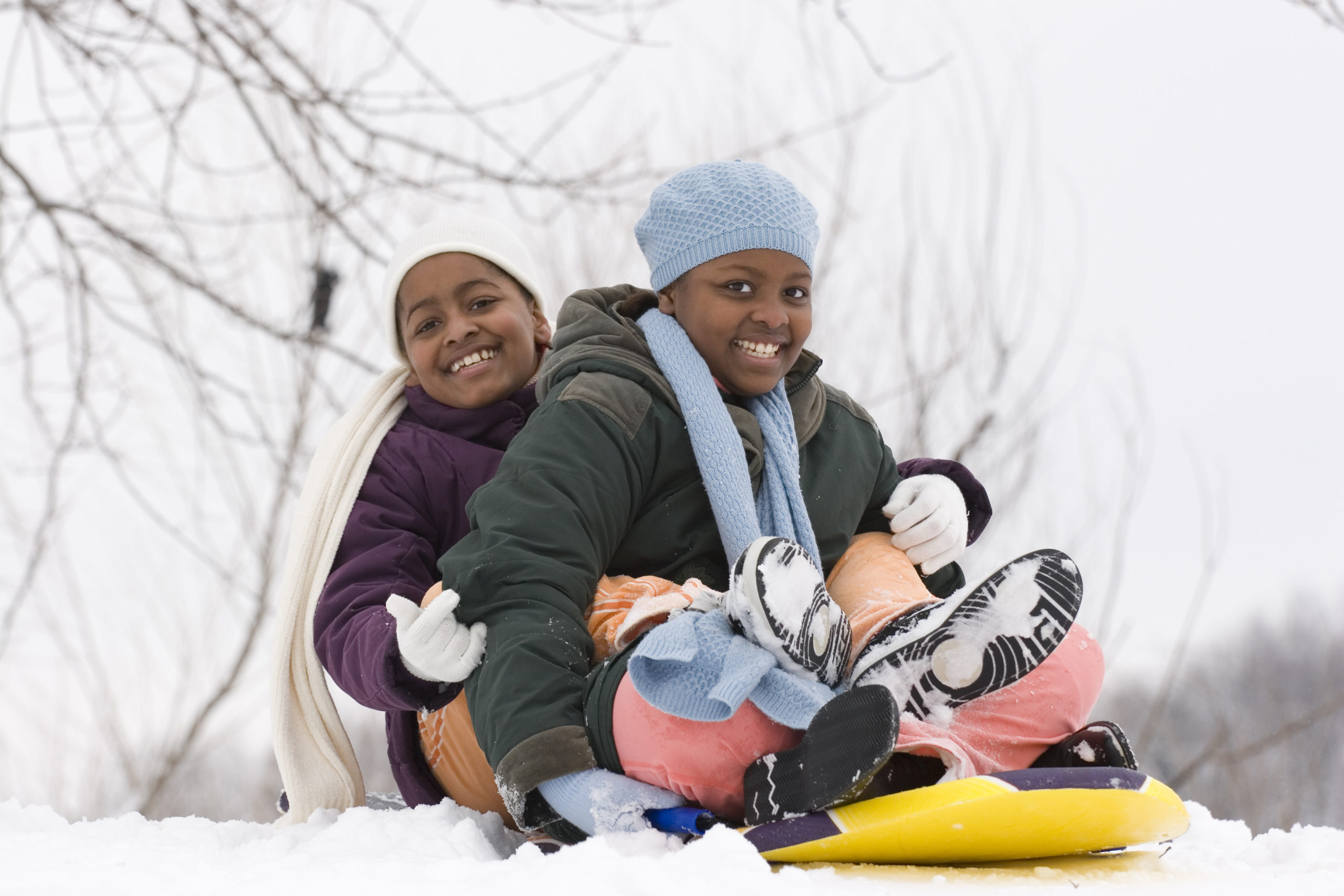 Two children smiling on a sled in the snow