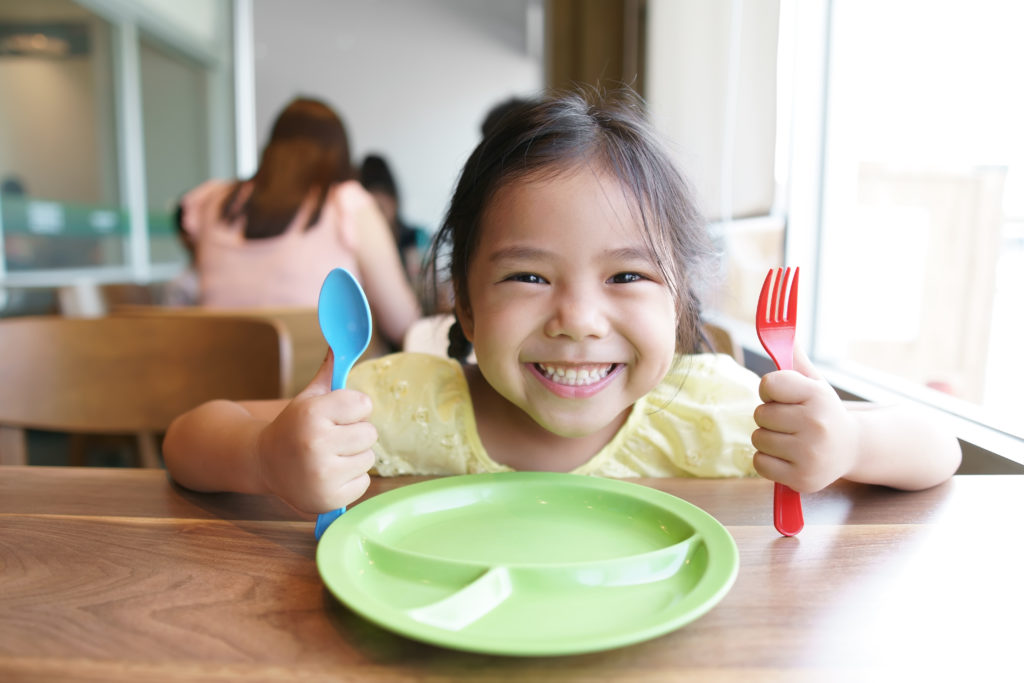 Child holding fork and knife at table