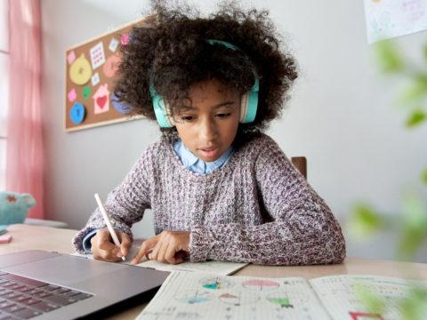 Girl wearing headphones and doing homework