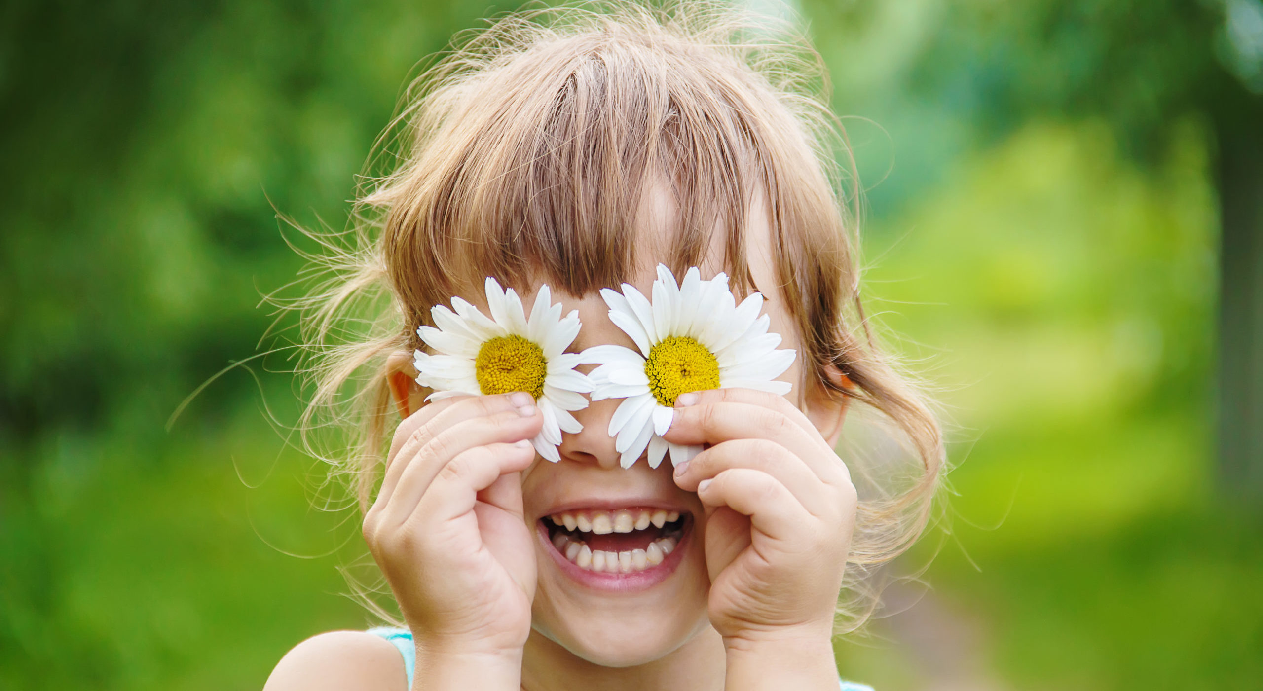 Child holding chamomile flowers in front of her eyes