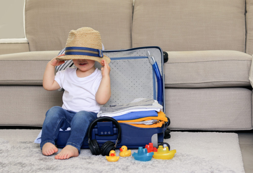 Child playing in packed suitcase
