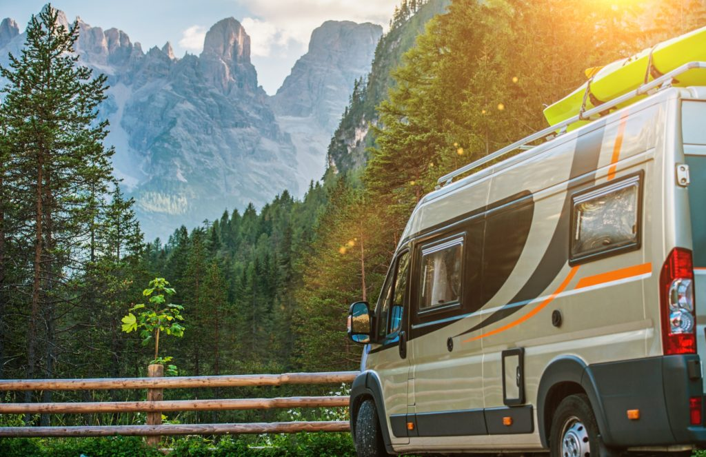 Class B Motorhome parked in front of a green forest