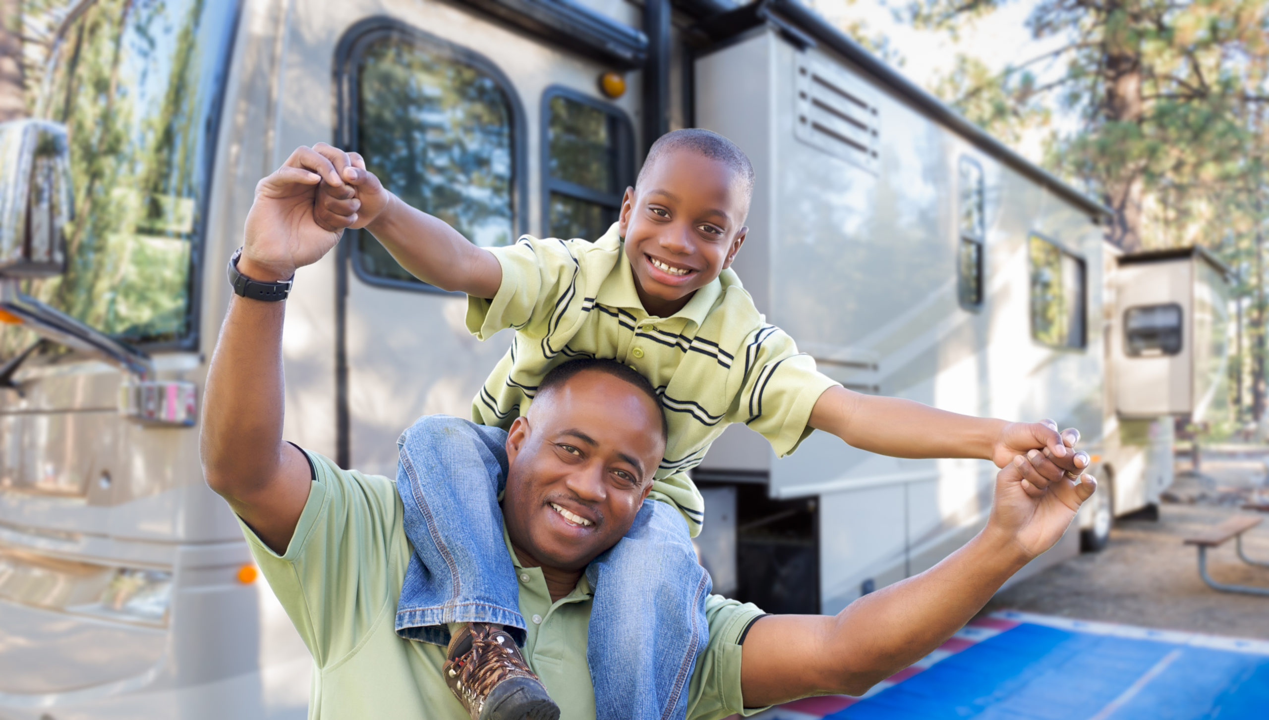 Son on his father's shoulders in front of their RV
