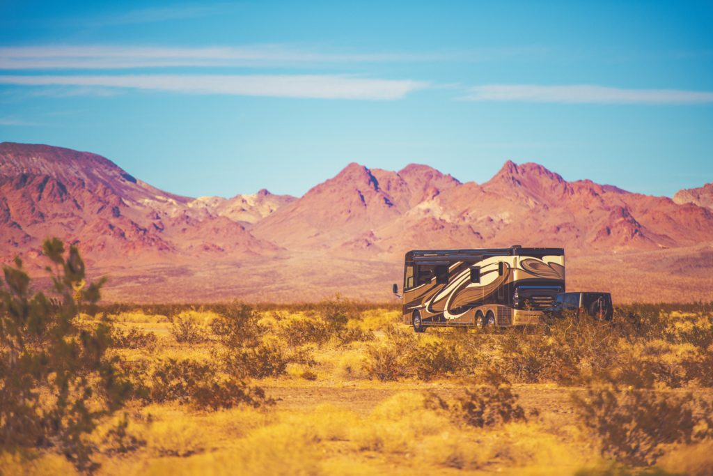 Class A Motorhome driving through red mountains