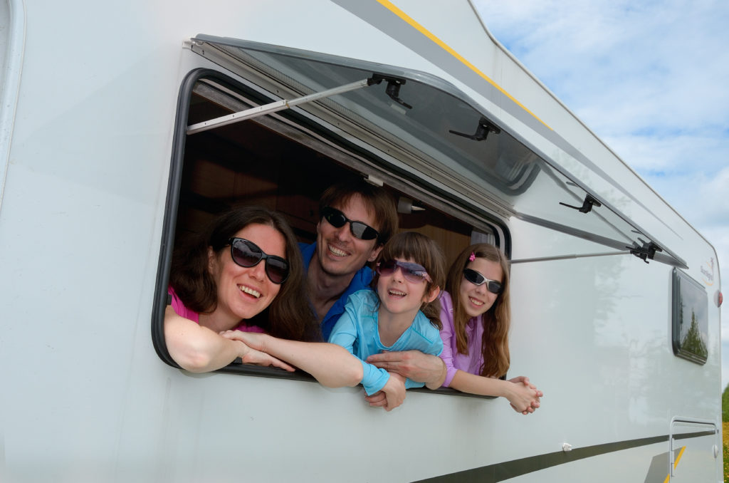 Family leaning out of the window of their RV