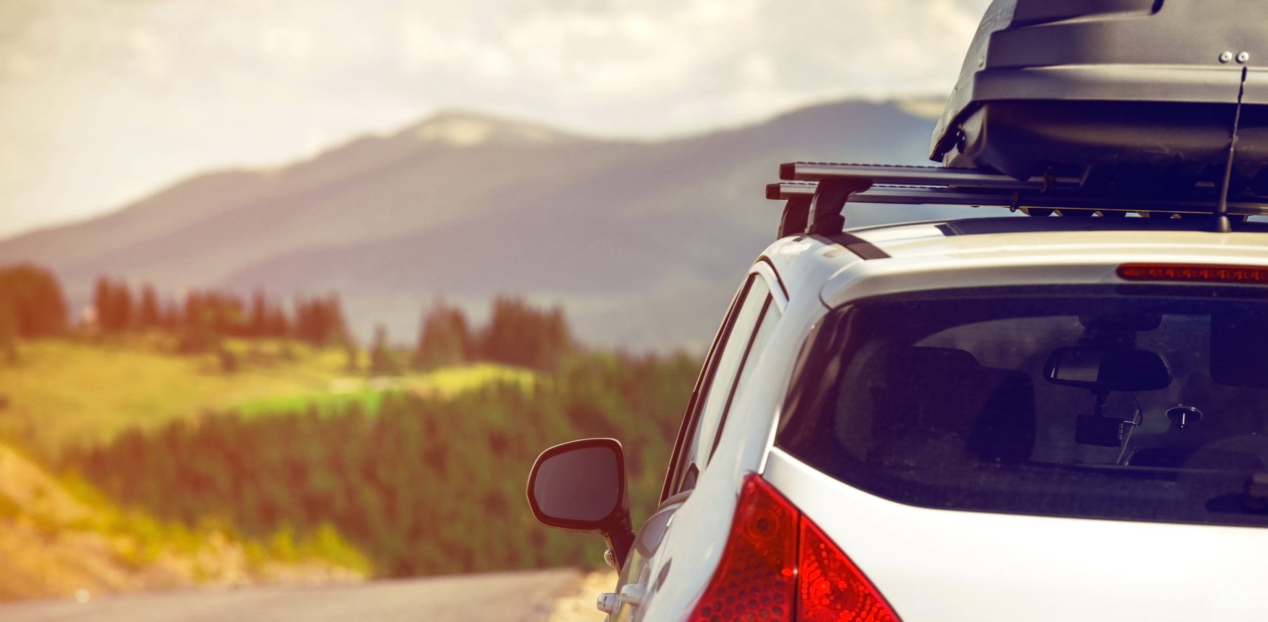 Car on a mountain road with a roof cargo carrier
