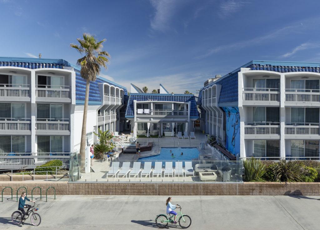 People biking in front of the Blue Sea Beach Hotel