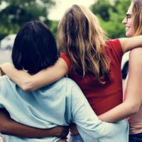 Four young women laugh and walk with their arms around each other