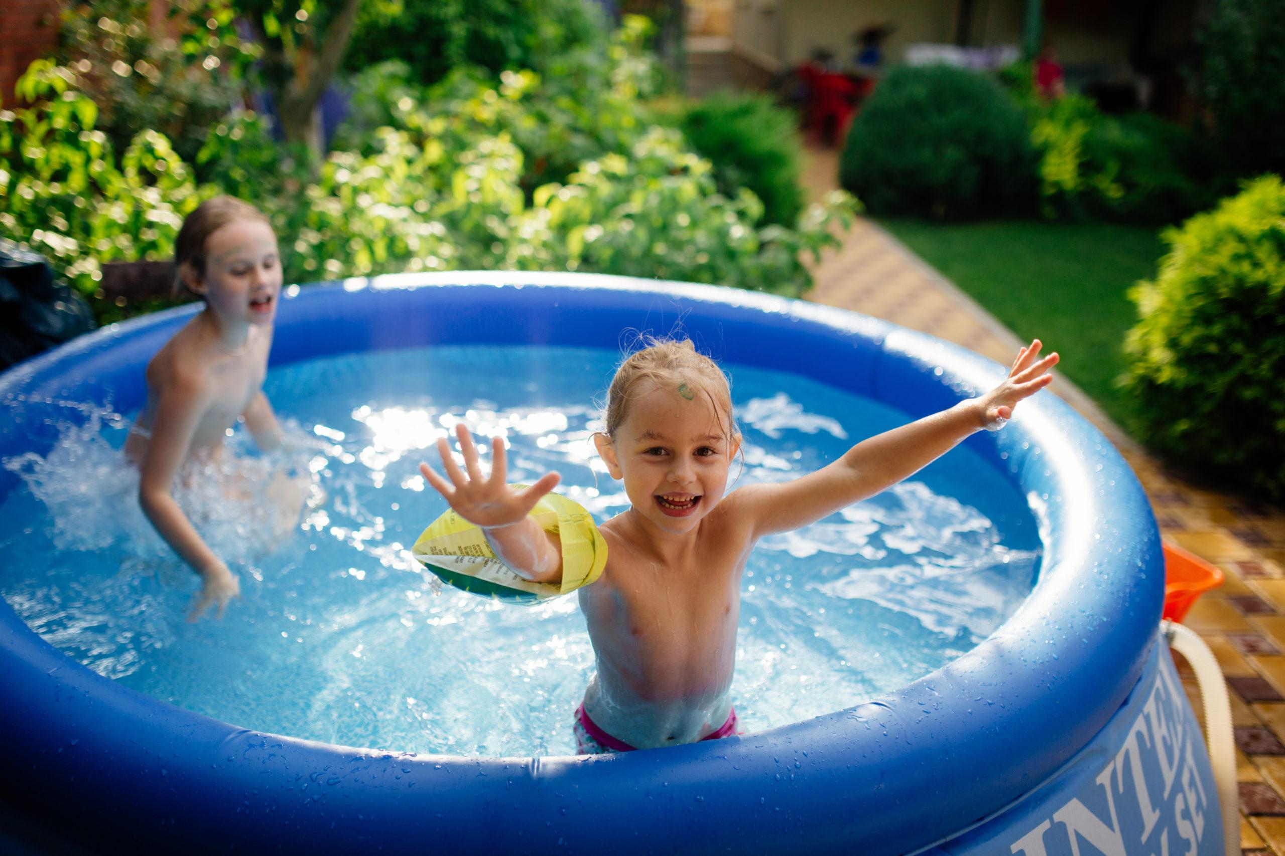 Two siblings splashing in kiddie pool