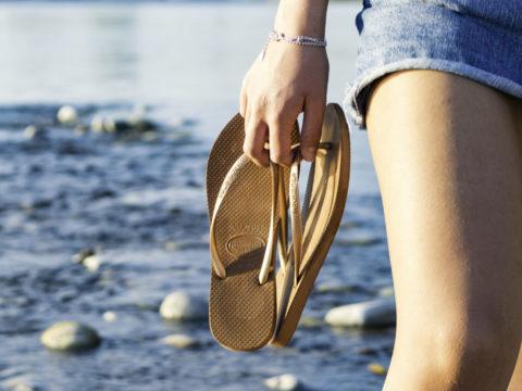 Woman holding flip flops on beach