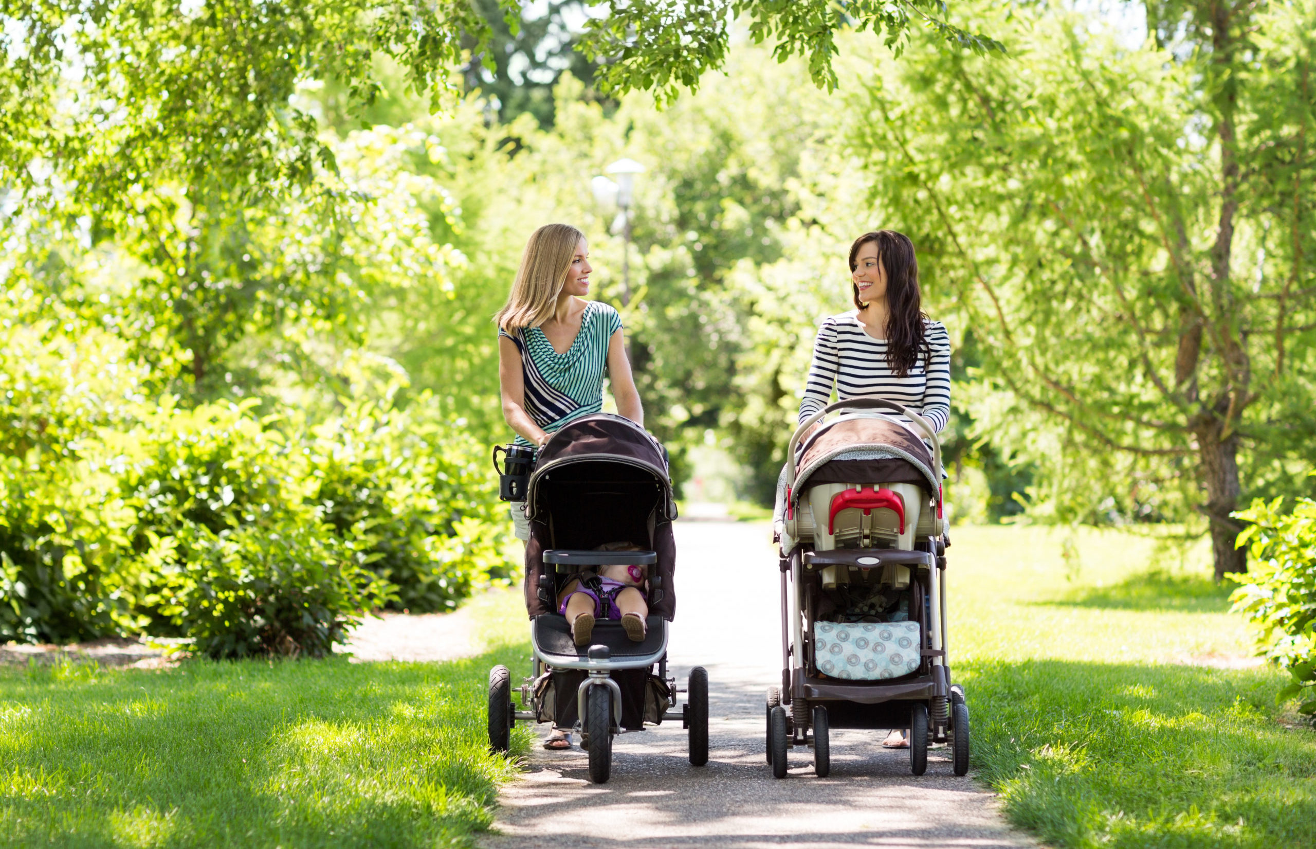 Two women pushing two babies in two strollers in the park