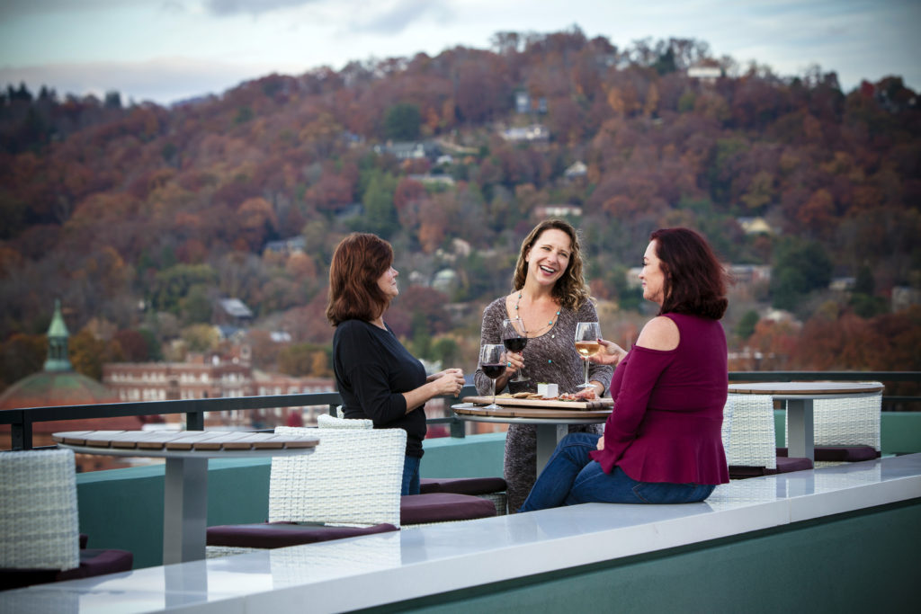 Three friends drinking wine on a patio overlooking fall foliage
