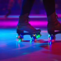 A person from the shins down, wearing a pair of roller skates in a dark roller rink with pink and purple lights