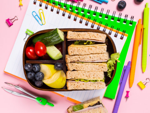 Flat-lay of fully packed school lunch box on top of notebooks and school supplies