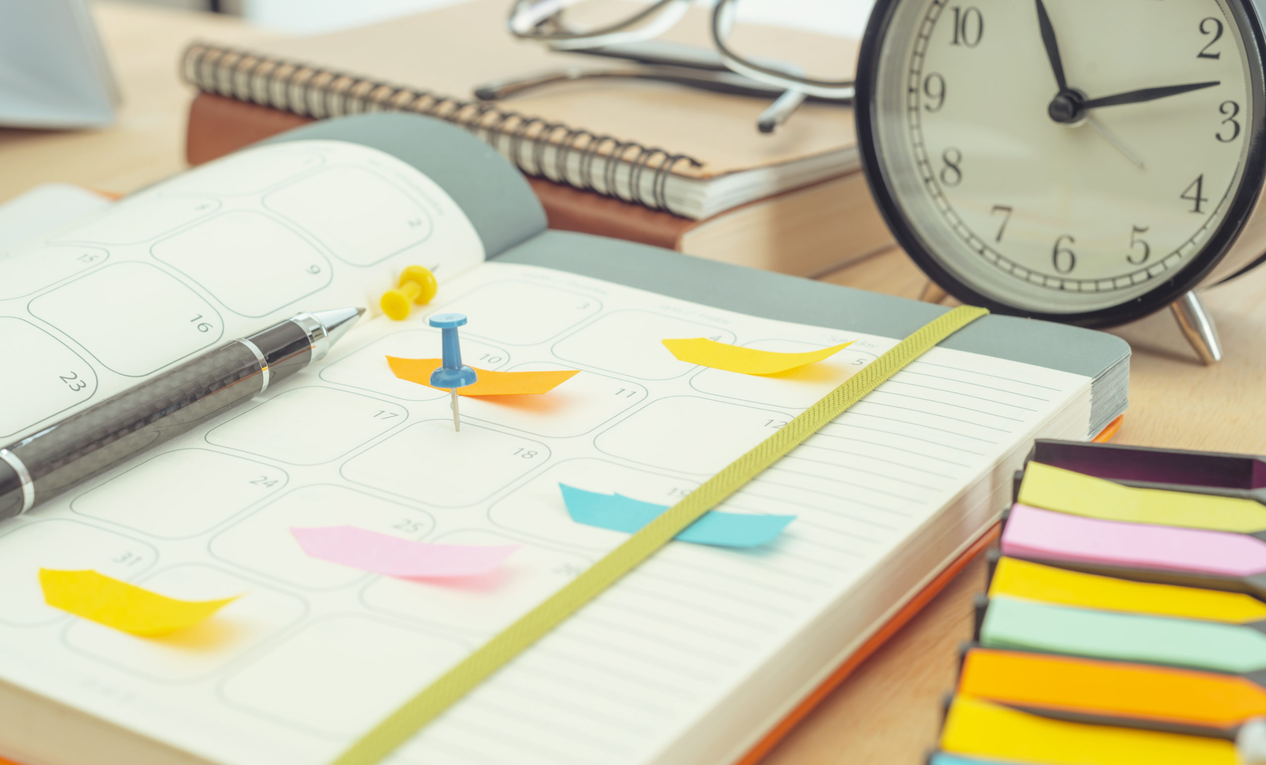 Daily planner open on a messy desk with pens, pins, glasses, sticky notes, and a clock