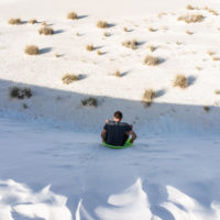 Man sliding down sand dune on sand sled