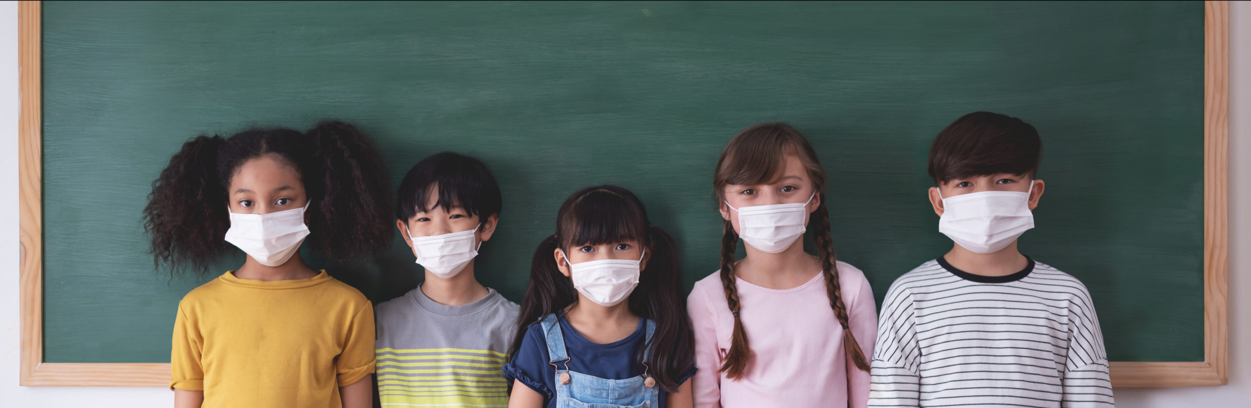 Children in front of a school chalkboard wearing protective face masks
