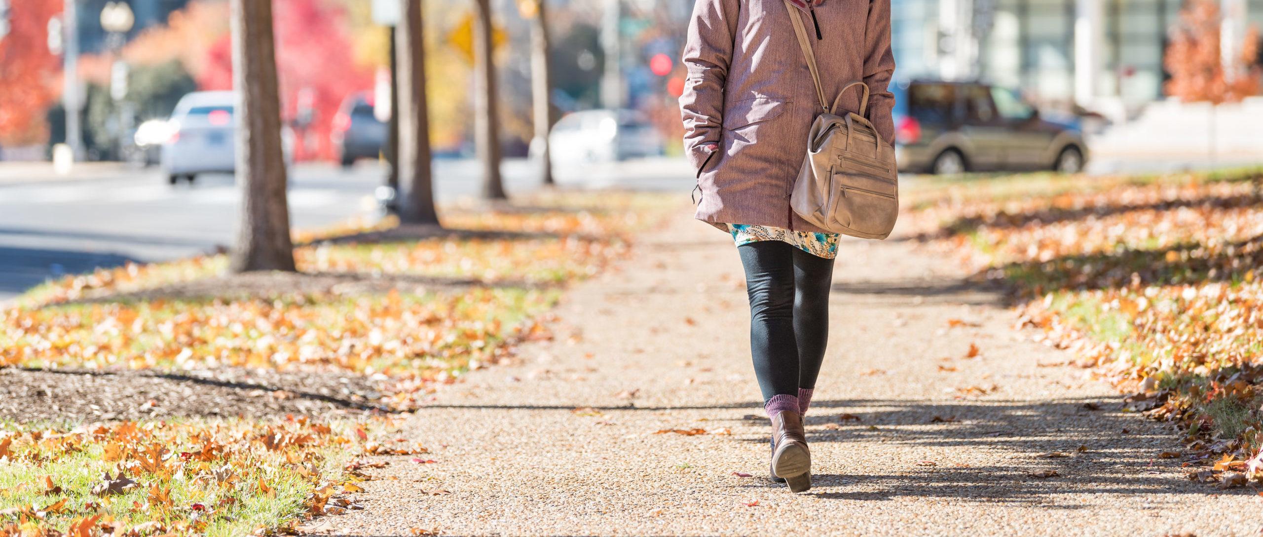 Woman walking down street in autumn