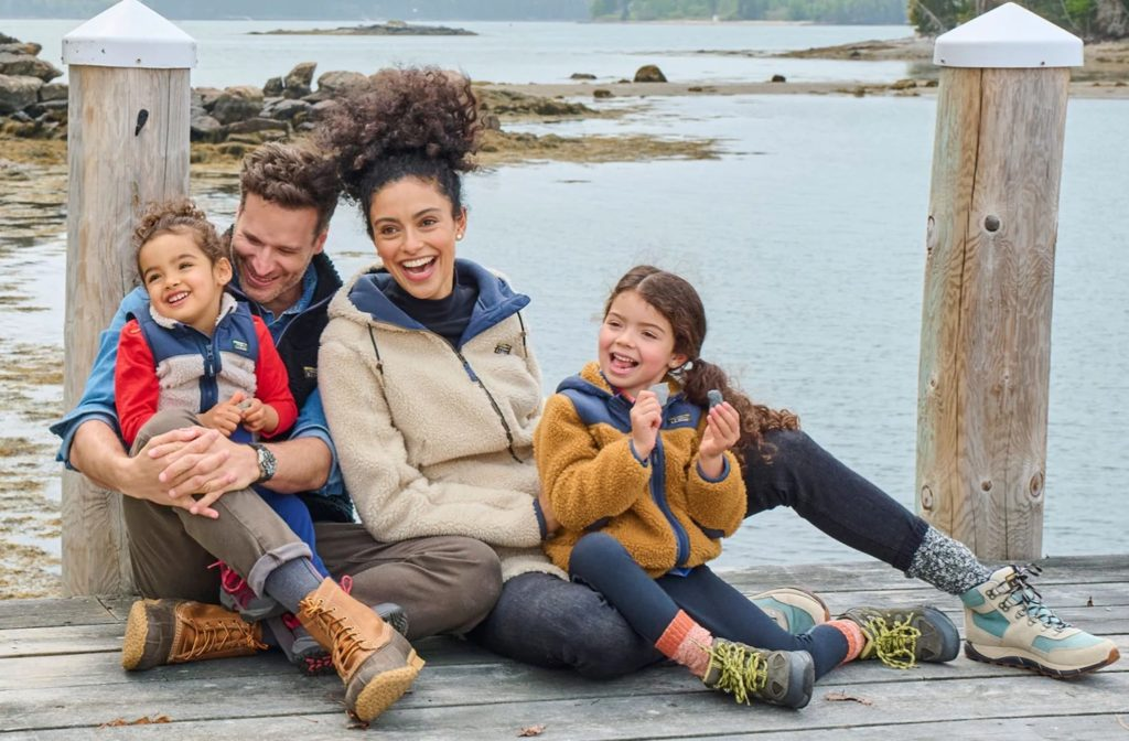 A family of four wearing warm clothes and sitting on an old wooden doc
