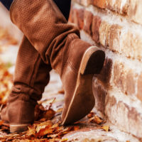 Person wearing tall fall boots, leaning against a brick wall and standing on fallen leaves