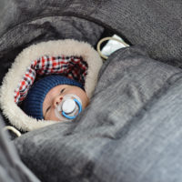Newborn baby bundled up for winter in a baby carrier