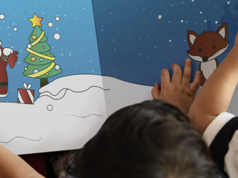 Over-the-shoulder view of three children reading a Christmas storybook